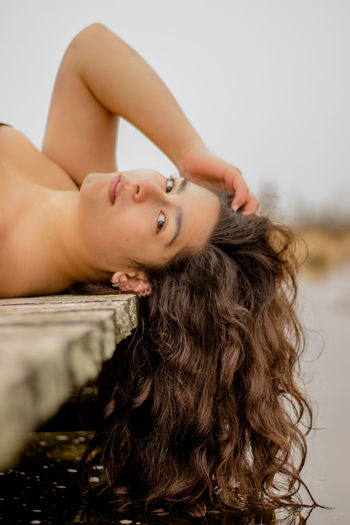 Portrait Of Young Woman Lying On Pier