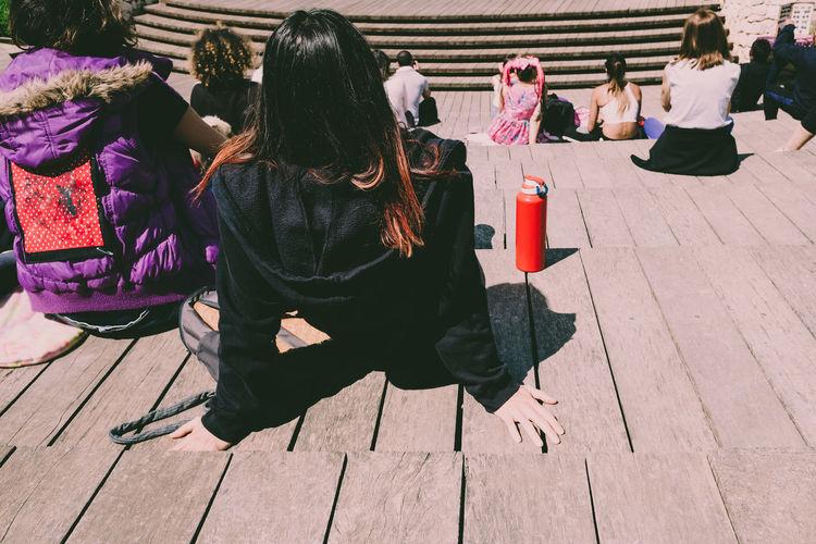 Rear view of women sitting on footpath