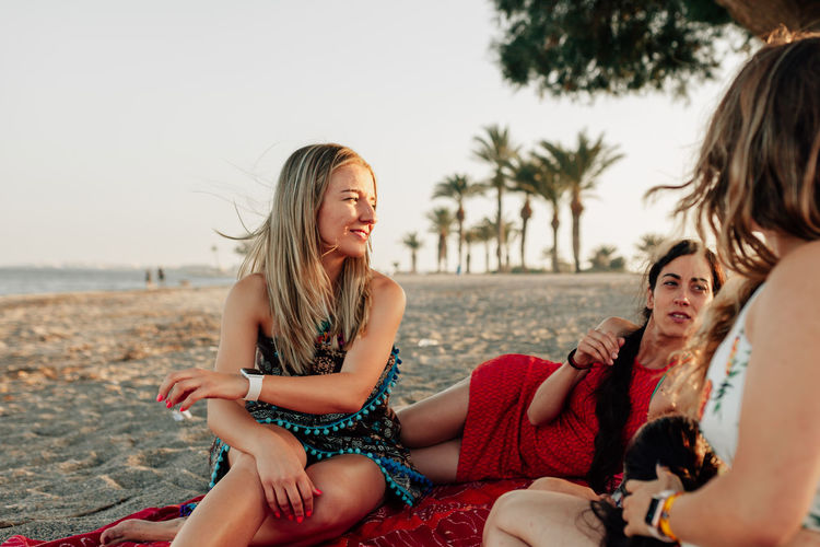Female friends talking at beach against sky during sunset