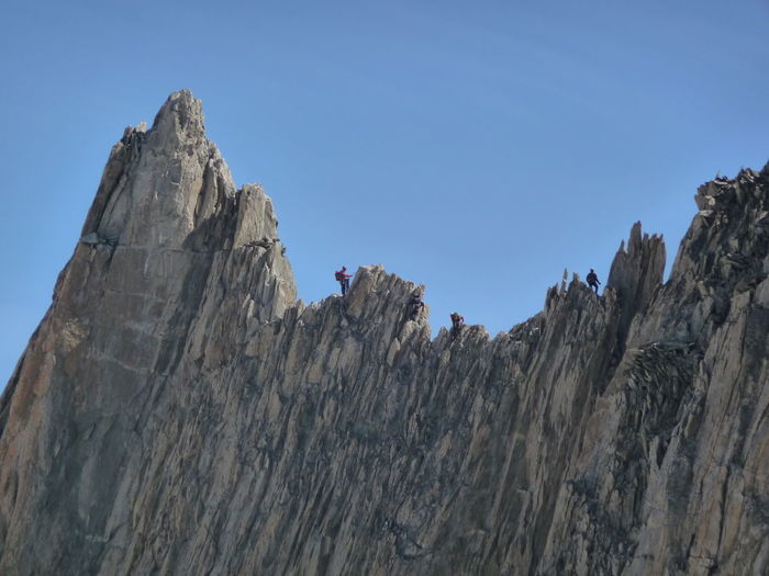 Low angle view of cliff against clear blue sky