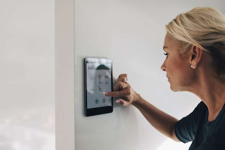 Portrait of young woman using mobile phone against wall