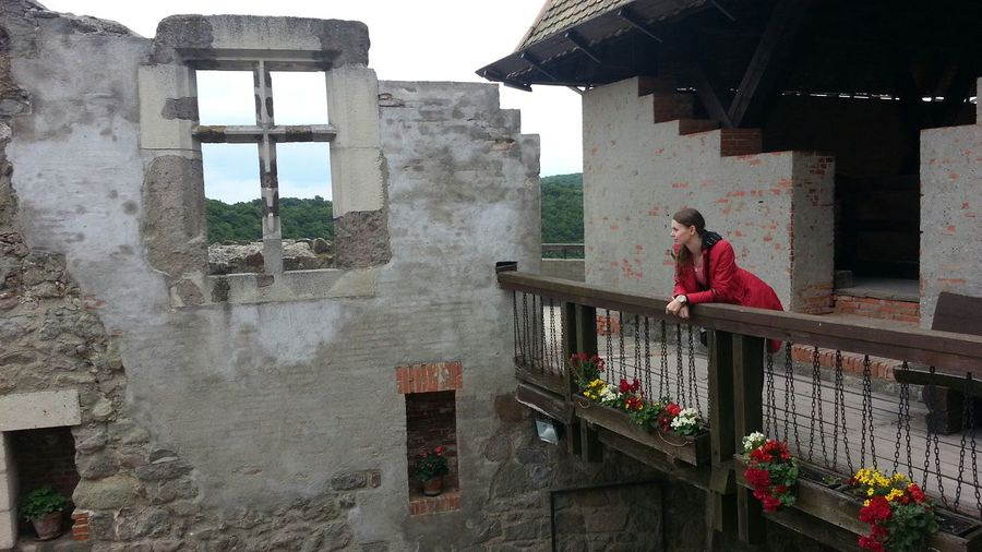 Woman standing at balcony by old building