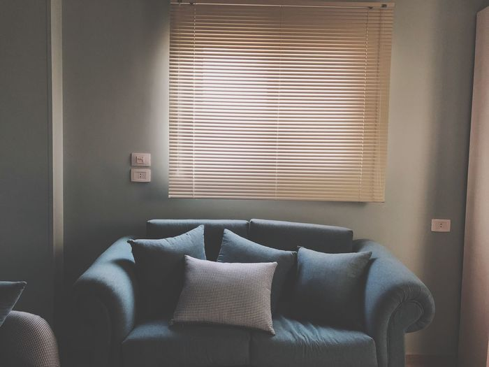 Cushions On Sofa By Window At Home