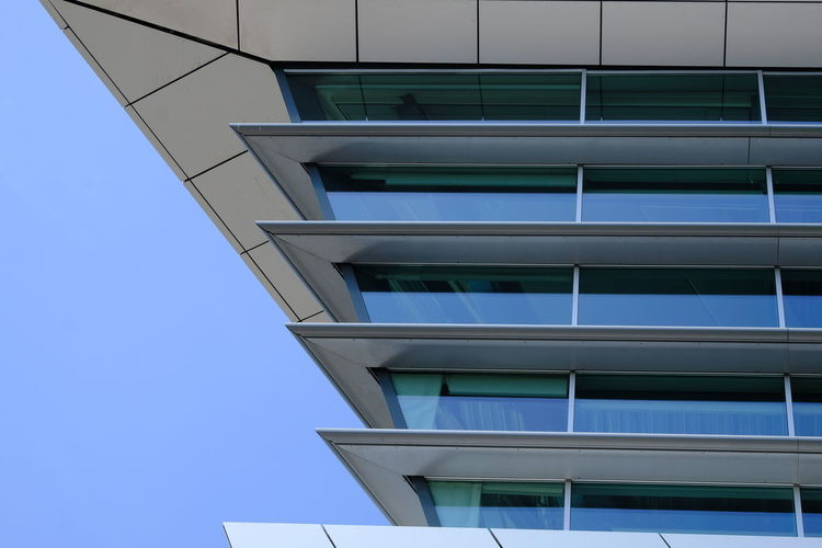 Low angle view of modern building against clear blue sky.