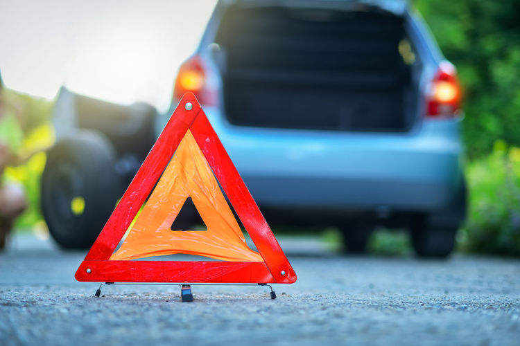 Changing the tire on a broken down car on a road with red warning triangle Road Car Assistance Problem Damaged Tire Flat Sign Driving Asphalt Trip Emergency Danger Auto Post Production Filter Vehicle Driver Drive Stop Help Street Stuck Repairs Service Transportation Business