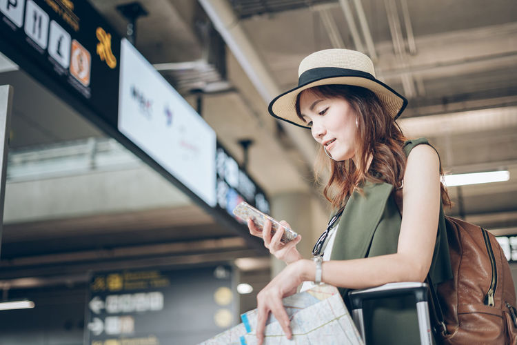 Woman using mobile phone while standing at airport terminal