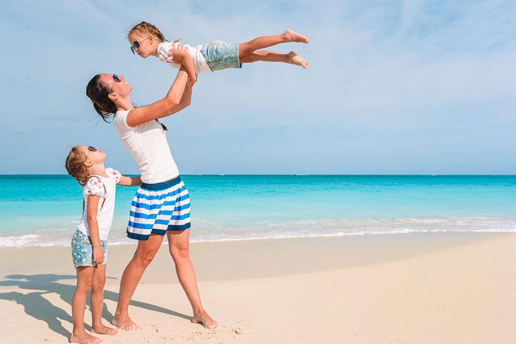 Full length of siblings on beach against sky