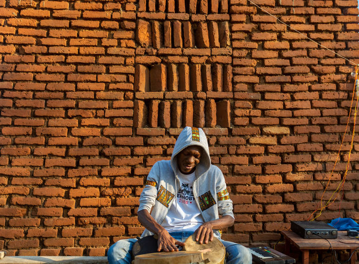 Full length of man sitting against brick wall playing a drum