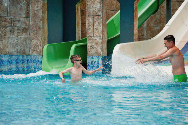 Happy boy with father enjoying in water park