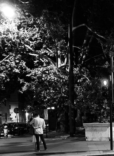 Rear view of man walking on street in city at night