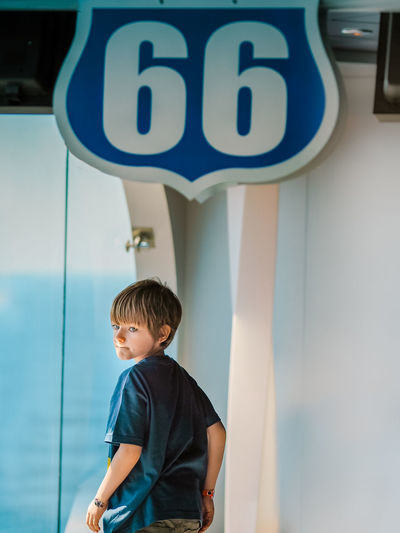 Boy standing against wall by door