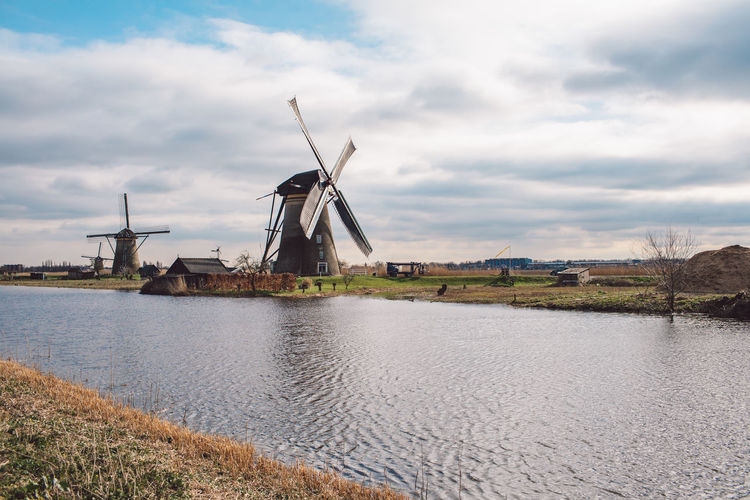 Traditional windmill by river against sky