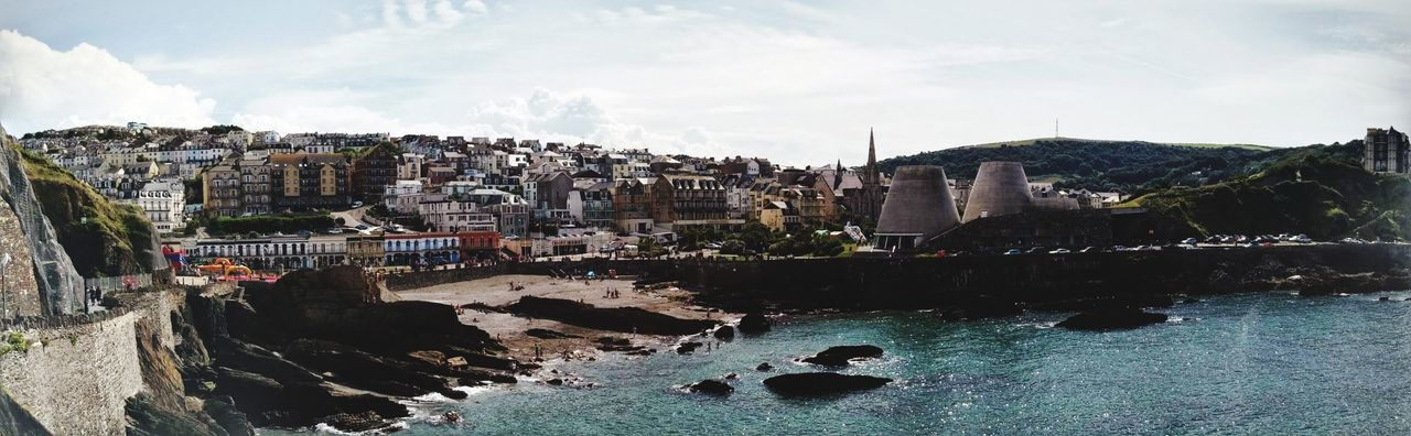Panoramic view of buildings by sea against sky