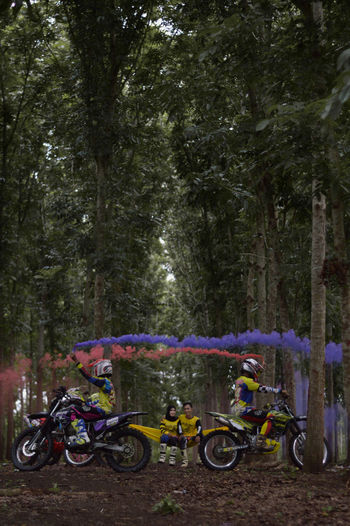 Motocross rider holding distress flares against couple at forest