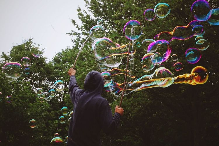 Rear view of man playing with bubbles