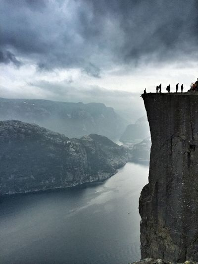 Silhouette people standing at preikestolen by river against cloudy sky