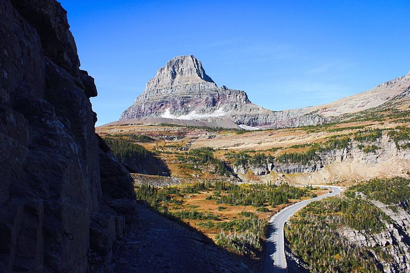 Scenic view of rocky mountains against blue sky at glacier national park