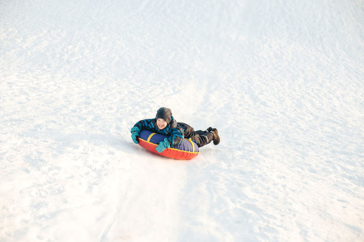 Full length of boy playing on snow outdoors