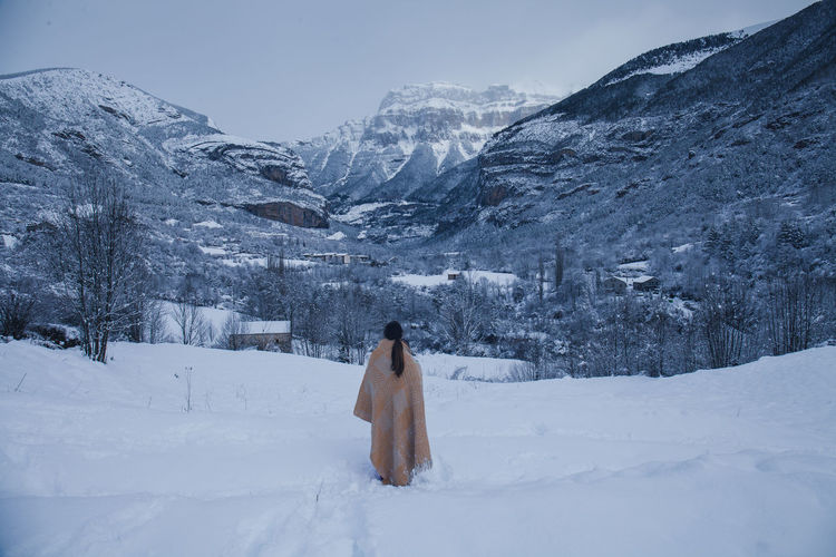 Rear view of woman wearing shawl while looking at snow covered mountain against sky