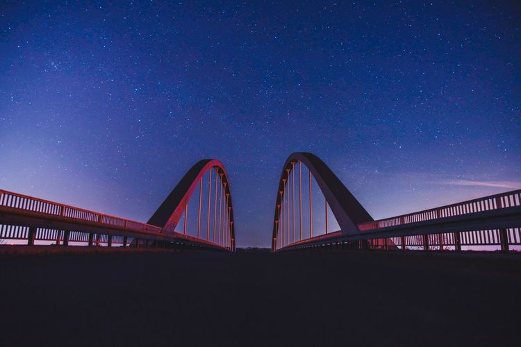 Diminishing perspective of bridge against star field at night