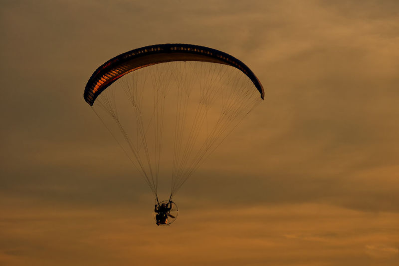 Low angle view of kite flying against sky during sunset