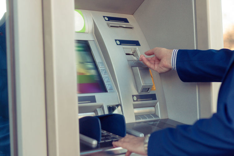 Midsection of man using atm machine