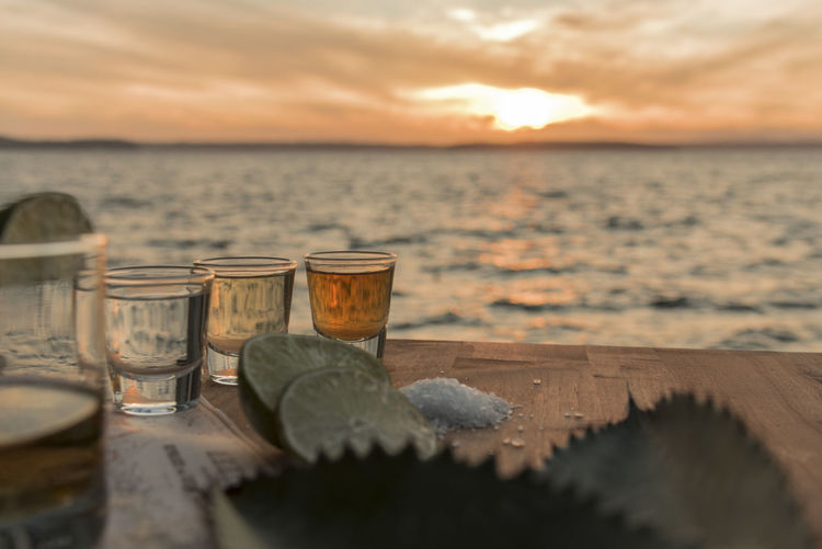 Tequila in shot glasses on table against sea during sunset