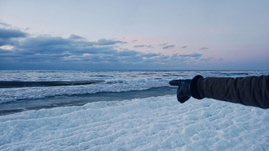 Close-up of person pointing at frozen sea against sky during sunset