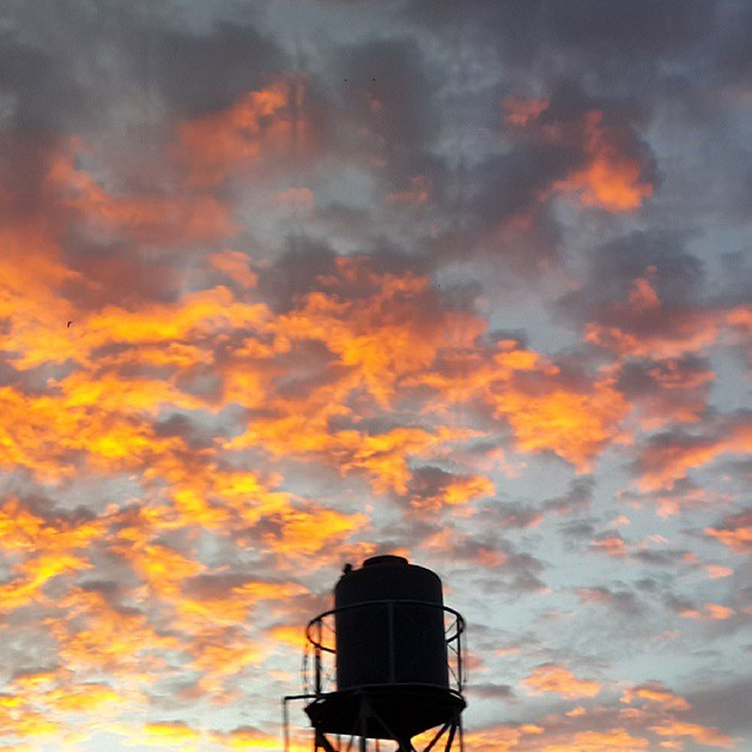 sunset, sky, low angle view, building exterior, orange color, cloud - sky, architecture, built structure, cloudy, silhouette, dramatic sky, cloud, high section, outdoors, weather, nature, beauty in nature, dusk, no people, scenics