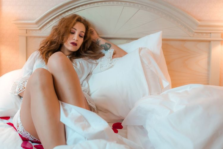 Seductive Woman Sitting On Bed