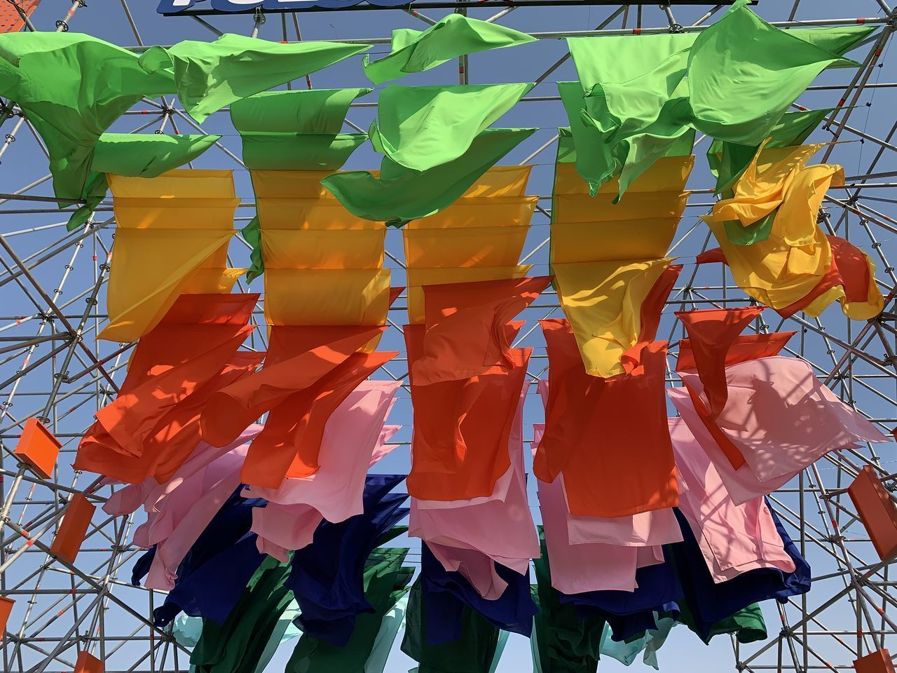 day, multi colored, nature, hanging, side by side, no people, green color, outdoors, in a row, textile, plant, clothing, yellow, large group of objects, orange color, focus on foreground, safety, repetition, leaf, flag, orange