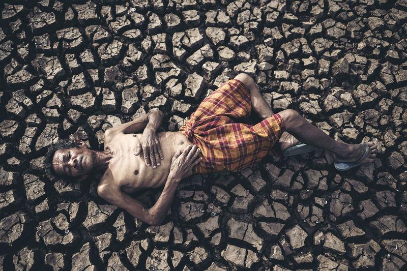 Full length of senior man with lying on cracked land