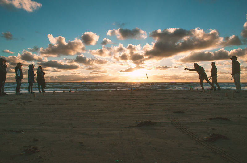 Silhouette people playing on beach against sky during sunset