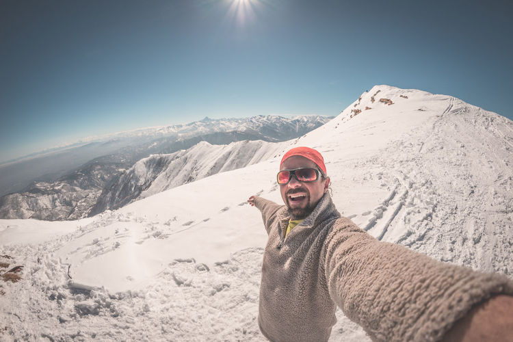 Portrait of man standing on snow covered mountain