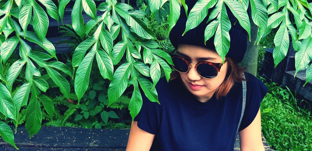 Portrait of young woman wearing sunglasses sitting against plants