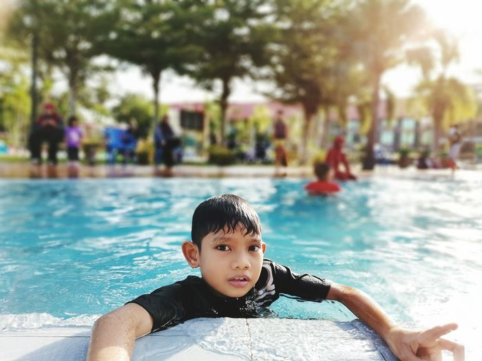 Portrait of happy boy in swimming pool at malaysia during school holiday