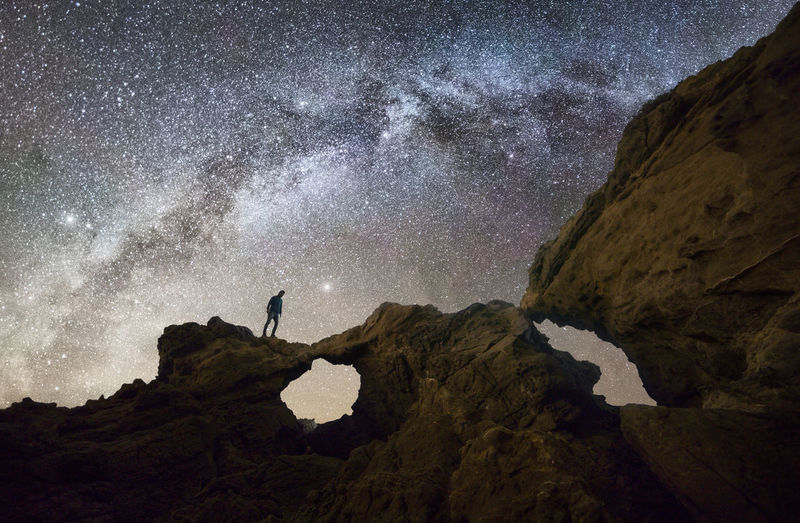 Man standing on rock formation against sky at night