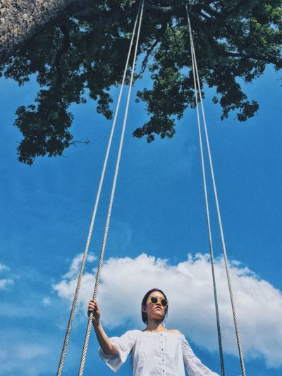 Low angle view of woman holding ropes while standing against sky