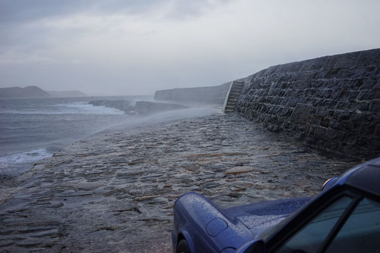 Scenic view of parked car in front of stormy beach