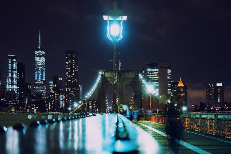 Illuminated lamppost on brooklyn bridge in city at night