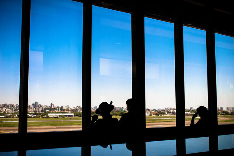 Silhouette people standing by window in waiting room at airport
