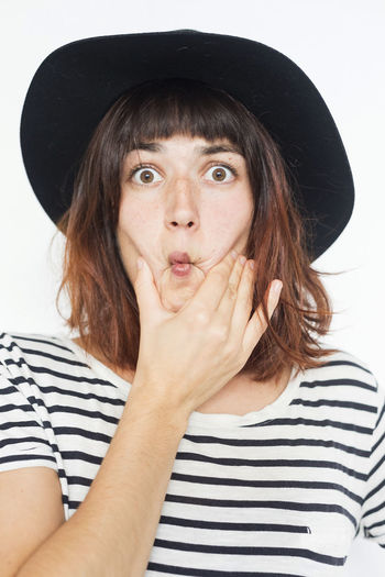 Portrait Of Young Woman Making Face Against White Background