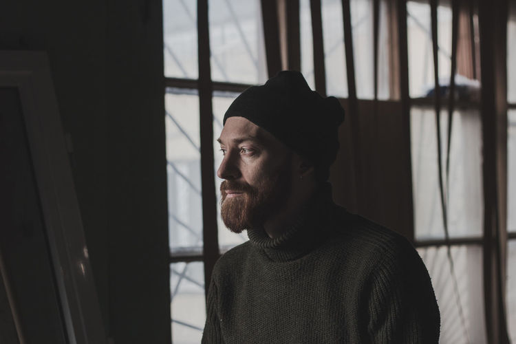 One Person Facial Hair Beard Real People Indoors  Window Lifestyles Headshot Young Men Portrait Leisure Activity Looking Men Casual Clothing Looking Away Clothing Hat Standing Contemplation