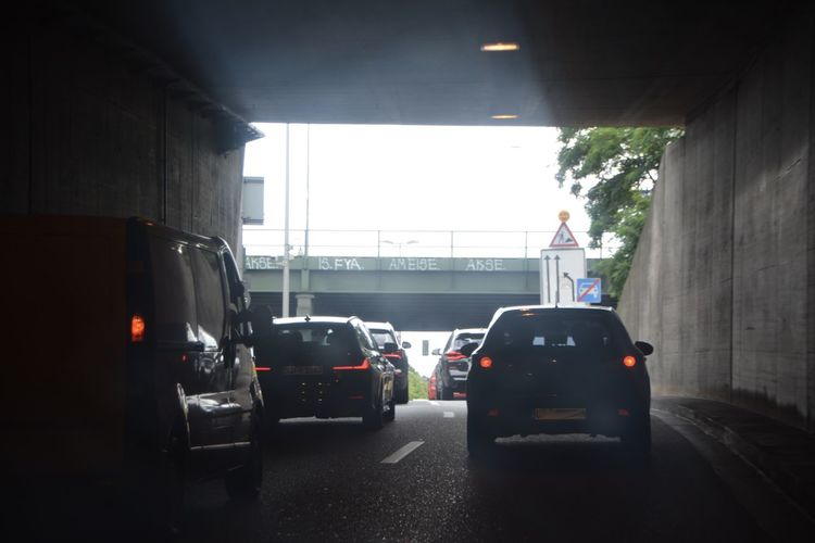 Rear view of vehicles on road in city