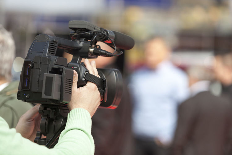 Rear view of journalist filming with television camera