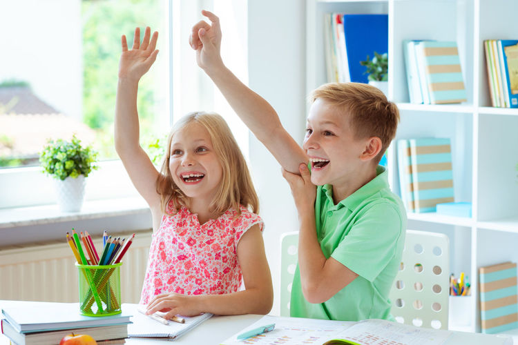 Brother and sister smiling with arm raised while sitting at home