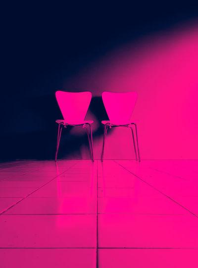 Empty chair on floor against wall