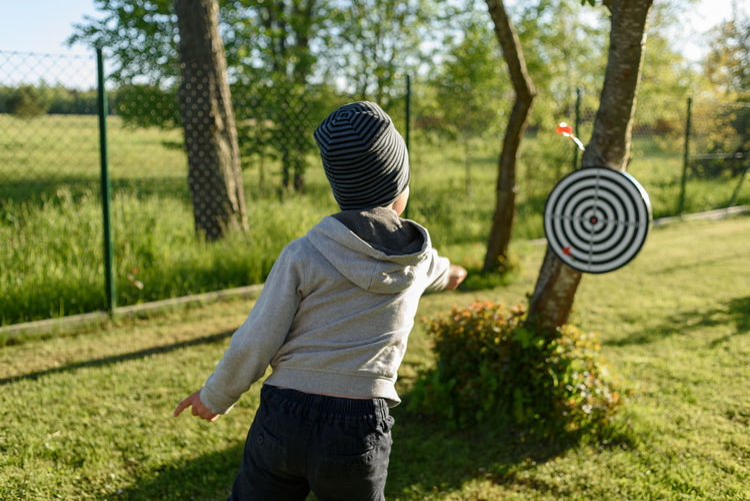 Rear view of boy playing dart
