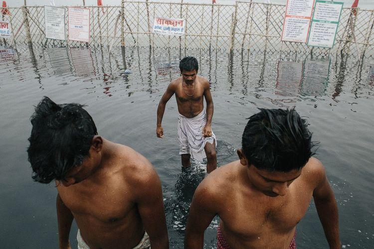 Rear view of shirtless man swimming in water