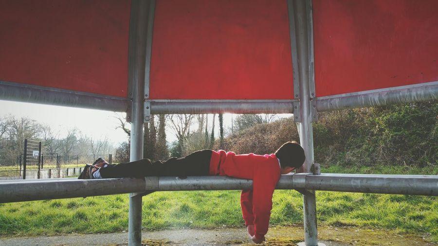 Full length of boy resting on gazebo at park